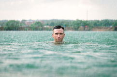 Man swimming in lake under the rain in thunderstorm Royalty Free Stock Photography