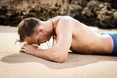 Man lying in sand on the beach. Man after swimming lying in sand on the beach Royalty Free Stock Photos