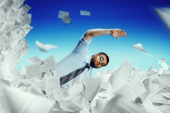 Man swimming in papers. Businessman in glasses swimming in papers Royalty Free Stock Photos