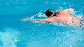 Man swimming in a pool doing the crawl. Man swimming in a cool blue swimming pool doing the crawl in mid stroke with his face in the water with splashing water Stock Photography