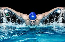 Man in swimming pool. Muscular young man in blue cap in swimming pool Royalty Free Stock Photo