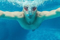 Man in swimming pool. Man in swim cap and googles under water in swimming pool Royalty Free Stock Images