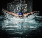Man in swimming pool. Young man in swimming cap and goggles swim using breaststroke technique Stock Photo