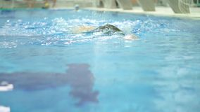 Man swimming in swimming pool towards the camera. Slow motion video stock video footage
