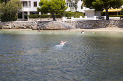 Man swimming to shore in Puerto Pollenca. Swimming in warm sea in Spain Stock Image