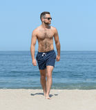 Man in swimming trunk son beach. Man wearing blue swimming trunks and sunglasses walking along sandy beach on sunny day Royalty Free Stock Photo