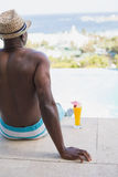 Man in swimming trunks relaxing poolside Royalty Free Stock Image