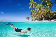 Man swimming underwater. Man swimming in a clear tropical waters in front of exotic island Stock Photo