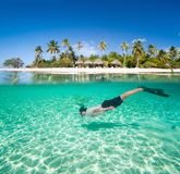 Man swimming underwater. Man swimming in a tropical lagoon in front of exotic island Stock Images