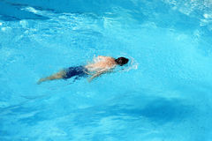 Man Swimming. A man swimming underwater in a pool Stock Image