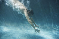 Man Swimming Underwater. Side view of middle aged man swimming underwater Royalty Free Stock Photos