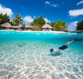 Man swimming underwater. Man swimming in a tropical lagoon in front of exotic island Stock Photography