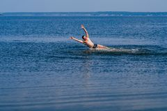 Man swims and having fun resting in water with the spray in summer. Man swims and having fun resting in the water with the spray in summer on the beach Stock Photography