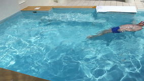 The man swims in the pool on a back, vignetting stock footage