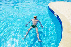 Man swims in the pool on a bright sunny day Royalty Free Stock Image