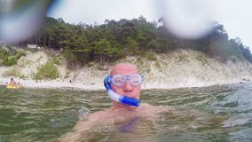 A man swims in the sea in glasses and with a tube for swimming stock footage