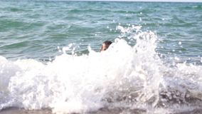 Man bathing in the sea. A man swims in the sea and looking at the big foamy sea wave stock video