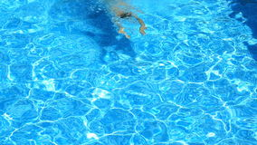 A man swims under the water in a pool with blue water. view from above. A man swims under the water in a pool with blue water. view from above stock video footage