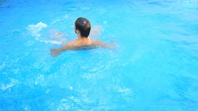 A man swims under the water in a pool with blue water. view from above. A man swims under the water in a pool with blue water. view from above stock footage