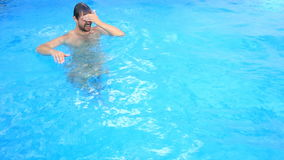 A man swims under the water in a pool with blue water. View from above. A man swims under the water in a pool with blue water. View from above stock video