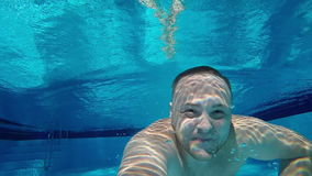 A man swims under the water in the pool with his eyes open, looking into the camera. Underwater Selfie. Slow motion video stock footage