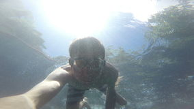 The man swims under the water. He shoots himself in the action camera. Underwater shooting. Swimming underwater mask on the face stock video footage