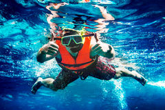 Man swims underwater and shows cool gesture stock image