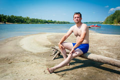 Man in swimshort. Sitting on log  the bank of river Royalty Free Stock Photo