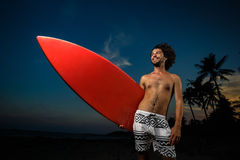 Man in swimsuit holding a surfboard. Young man in swimsuit walking on the beach with surfboard in sunset Stock Image