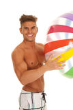 Man in swimsuit smiling holding beachball Royalty Free Stock Photos