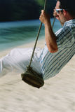Man on swing at beach Royalty Free Stock Photo