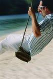 Man on swing at beach.  Royalty Free Stock Photo