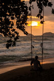 Man on Swing at Sunset Beach Stock Images