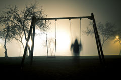 Man on the swing in foggy and mysterious park at night. Stock Image