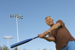 Man Swinging Baseball Bat Outdoors Stock Photography