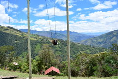 Man swinging in the end-of-the-world swing in the town of Banos, Ecuador. The small town of Banos or Baños, in Ecuador, is famous for it`s tree house and the ` stock photos