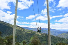 Man swinging in the end-of-the-world swing in the town of Banos, Ecuador. The small town of Banos or Baños, in Ecuador, is famous for it`s tree house and the royalty free stock image