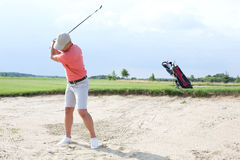 Man swinging at golf course against sky Royalty Free Stock Photo