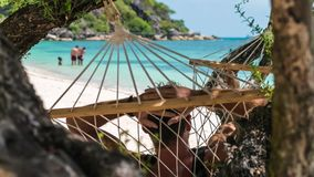Man swinging relaxed in a hammock on the beach in front of the beautiful blue ocean. Hiding him from the sun in the stock video