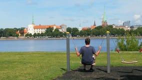 man swinging on swing, watching riga view, latvia