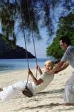 Man swinging woman on swing at beach.  Royalty Free Stock Photo