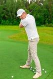 Man swings to strike a golf club Stock Photo