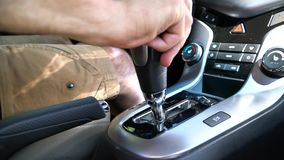 A man switches the selector of the automatic transmission in Parking mode. A man sitting in the car and switches the selector of the automatic transmission in stock video footage