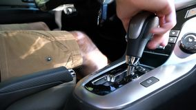 A man switches the selector of the automatic transmission in reverse mode. A man sitting in the car and switches the selector of the automatic transmission in stock footage