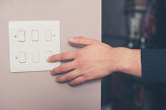 Man switching on lights. A young man's hand is switching on a light switch at home Stock Photo