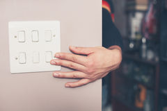 Man switching on lights. A young man's hand is switching on a light switch at home Stock Photography