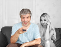 Man switching TV channel on remote control boring wife Royalty Free Stock Image
