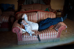 Man switching TV channels on sofa at night Royalty Free Stock Photography