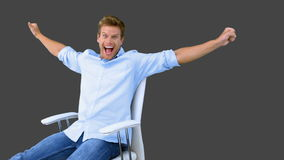 Man on swivel chair raising arms to show his success on grey screen Royalty Free Stock Image