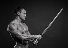 Man with sword. Shirtless young man posing with katana sword Stock Image